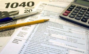 US Tax forms with pen pencil glasses calculator